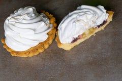 Läcker merengueefterrätt Citrontartlet som är syrlig med med maräng, äppledriftstopp inom på bakgrund för tabell för grå färgsten arkivfoto