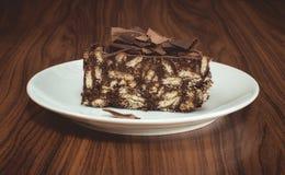 Läcker mosaikchoklad och den ljusbruna kakan tjänade som i den vita plattan på trätabellen Royaltyfria Bilder