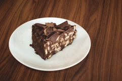Läcker mosaikchoklad och den ljusbruna kakan tjänade som i den vita plattan på trätabellen Fotografering för Bildbyråer