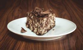 Läcker mosaikchoklad och den ljusbruna kakan tjänade som i den vita plattan på trätabellen Royaltyfri Fotografi
