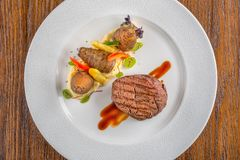 Läcker nötköttbiff med sås och grönsaken som tjänas som på den vita plattan, modern gastronomi, michelinrestaurang arkivfoton
