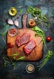 Läcker nötköttbiff på tappningskärbräda med nya olika ingredienser för smaklig matlagning på lantlig träbakgrund royaltyfria foton