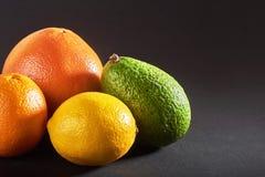 Läcker ny apelsin, grapefrukt, avokado, citron som isoleras på en svart bakgrund arkivbilder