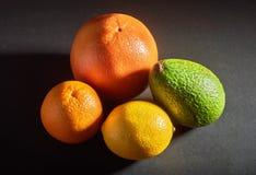 Läcker ny apelsin, grapefrukt, avokado, citron som isoleras på en svart bakgrund royaltyfria bilder