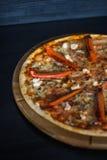 Läcker ny pizza på svart bakgrund Arkivbilder