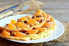 Läcker omelett med frukt, muttrar och choklad på plattan Stekt omelett som är välfylld med nya mandarines, valnötter Arkivbild