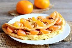 Läcker omelett med frukt och muttrar på plattan och på trätabellen Stekt omelett som är välfylld med nya mandarines och valnötter Royaltyfri Foto
