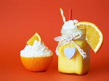 Läcker orange coctail med kräm i en härlig krus på en bri Royaltyfri Fotografi