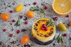 Läcker orange ostkaka i en glass ramekin fotografering för bildbyråer