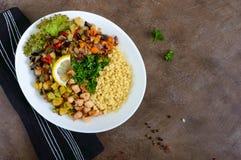 Läcker orientalisk salladtabbouleh Couscous med stekt grönsaker och höna på en vit platta fotografering för bildbyråer