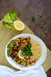 Läcker orientalisk salladtabbouleh Couscous med stekt grönsaker och höna på en vit platta arkivbilder