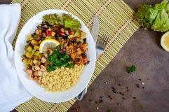 Läcker orientalisk salladtabbouleh Couscous med stekt grönsaker och höna på en vit platta arkivfoto