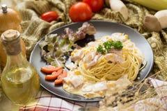 Läcker pastacarbonara med bacon och parmesan i en svart pilbåge Royaltyfri Foto