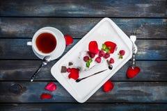 Läcker Pavlova kaka med en kopp te Nya hallon på en vit platta med rosa kronblad Top beskådar härligt arkivfoton