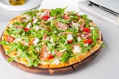 Läcker pizza för selektiv fokus med skivor för hamon och för körsbärsröd tomat, parmezan ost och arugula på träbrädet på t Royaltyfria Foton