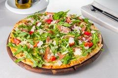 Läcker pizza för selektiv fokus med skivor för hamon och för körsbärsröd tomat, parmezan ost och arugula på träbrädet på t Royaltyfri Foto