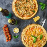 Läcker pizza med bacon, ost, tomaten och öl på mörk bakgrund Lekmanna- lägenhet Top beskådar Läcker matbakgrund arkivfoton