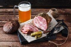 Läcker rökt skinka på ett blackwoodenbräde med öl och knipor royaltyfri fotografi