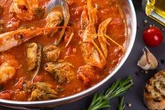 Läcker ragu med räkor i tomatsås Tjänat som i en stekpanna på en grå bakgrund Arkivfoto