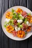 Läcker romantisk sallad med mozzarellaen, skinka, aprikos grillade och den nya grönsallatnärbilden på en platta Vertikal b?sta si arkivbild