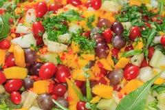 Läcker sallad av grönsaker och frukter Grönsallat tomat, persilja, arugula, druva, mango, melon royaltyfria foton
