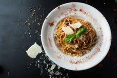 Läcker spagetti bolognese med ost och kryddor och kött Royaltyfria Bilder