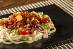 Läcker spagettisallad med räka, tomaten och pupunhaen gömma i handflatan royaltyfri bild