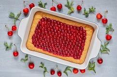 Läcker sund efterrätt - körsbärsröd paj i den stekheta maträtten på det gråa köksbordet Kallt syrligt för sommar som dekoreras me arkivfoton