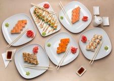 Läcker sushi på olika plattor på tabellen Royaltyfria Foton