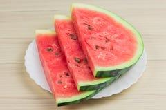 Läcker vattenmelon på en ljus träbakgrund Tre skivor av mogen röd vattenmelon för bär på ett vitt plattaanseende Arkivfoto
