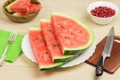 Läcker vattenmelon på en ljus träbakgrund Tre skivor av mogen röd vattenmelon för bär på ett vitt plattaanseende Royaltyfri Bild