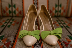 Läckerbiten färgrika skor för kvinna` s i par, med stor grön mockaskinn bugar på en bakgrund med etniska och stam- detaljer Arkivbilder
