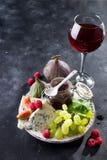 Läckerhetädelostar, frukt och driftstopp i krus med rött vin i exponeringsglas på svart kritiserar stenbakgrund, kopieringsutrymm arkivfoto