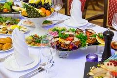 Läckerheter, mellanmål och frukt på den festliga tabellen i restaurangen Beröm catering sallader för fruktsaft för druvor för fru royaltyfri bild