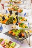Läckerheter, mellanmål och frukt på den festliga tabellen i restaurangen Beröm catering sallader för fruktsaft för druvor för fru royaltyfria bilder