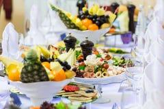 Läckerheter, mellanmål och frukt på den festliga tabellen i restaurangen Beröm catering sallader för fruktsaft för druvor för fru arkivfoto