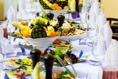 Läckerheter, mellanmål och frukt på den festliga tabellen i restaurangen Beröm catering sallader för fruktsaft för druvor för fru arkivbild