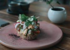 Läckert avokadorostat bröd med artisanal bröd på en rosa platta royaltyfria bilder