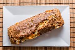 Läckert bröd med ost på den vita plattan Royaltyfri Bild