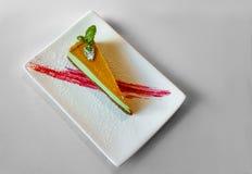 Läckert färgglat stycke av kakaefterrätten på en vit platta Royaltyfri Bild