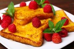 Läckert franskt rostat bröd med hallon och honung Arkivfoto