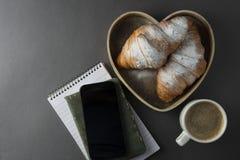 Läckert frukostkaffe med gifflet formad askhjärta Arbetstabell med den smarta telefonen Fransk bakelse och kopp kaffe arkivbilder
