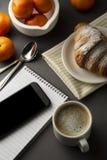 Läckert frukostkaffe med gifflet och citrusfrukter formad askhjärta Arbetstabell med den smarta telefonen Fransk bakelse och kopp royaltyfria bilder