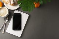 Läckert frukostkaffe med gifflet och citrusfrukter formad askhjärta Arbetstabell med den smarta telefonen Fransk bakelse och kopp arkivbild