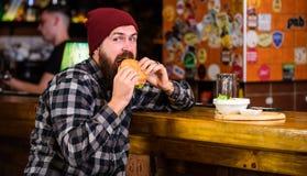 Läckert hamburgarebegrepp Tyck om smak av den nya hamburgaren Äter den hungriga mannen för hipsteren hamburgaren Mannen med skägg arkivfoton