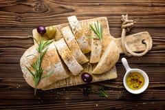 Läckert hemlagat italienskt ciabattabröd med olivolja och oliv på trälantlig bakgrund, ovanför sikt, utrymme för text royaltyfria bilder