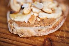 Läckert jordnötsmör, banan och öppen vänd mot smörgås för kasju royaltyfri bild