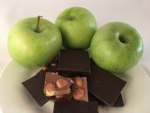 Läckert mellanmål - det gröna äpplet och choklad - closeup på vit bakgrund royaltyfri foto