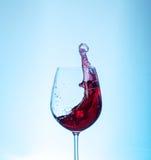 Läckert rött vin i ett exponeringsglas på en blå bakgrund mot som kroken för hang för dollar för bakgrundsbetebegrepp den gråa Arkivbild