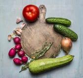 Läckert sortiment av nya grönsaker för lantgård runt om en rund skärbrädaställetext, ram på trälantlig bakgrundsöverkant VI Arkivbilder